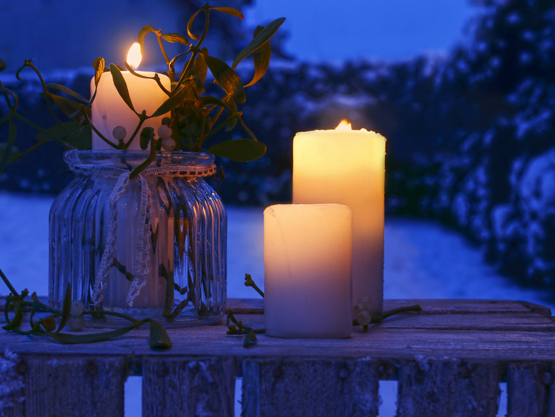 Candles decorated with mistletoe on rustic wooden table in winter garden